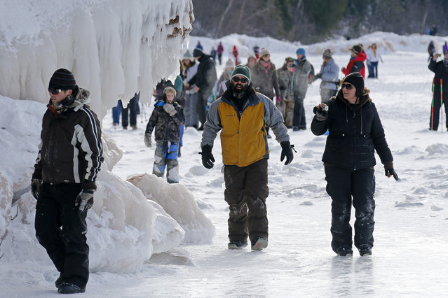 In this February 2, 2014 photo people visit the caves at  Apostle Islands National Lakeshore in northern Wisconsin, transformed into a dazzling display of ice sculptures by the arctic siege gripping the Upper Midwest. (Photo by Brian Peterson/AP Photo/Minneapolis Star Tribune)