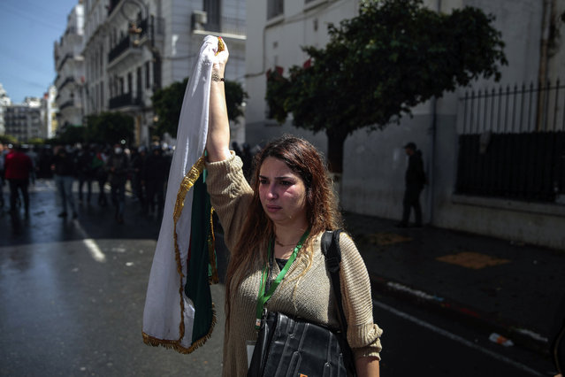A woman waves an Algerian flag after police attempted to disperse a demonstration for students in Algiers, Algeria, Tuesday, April 9, 2019. Algerian police used pepper spray and water cannon to break up a group of students protesting in the country's capital, less than an hour after the country's parliament chose an interim leader. (Photo by Mosa'ab Elshamy/AP Photo)