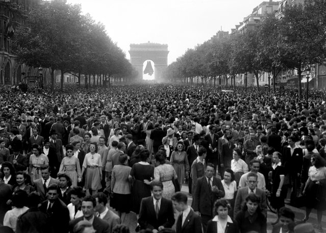 Picture dated of May 8, 1945 showing people gathering at the Champs Elysees Avenue, in front of the Triumphal Arch (Arc de Triomphe) as Parisians celebrate the unconditionnal German capitulation in the streets of Paris, at the end of the second World War. (Photo by AFP/Getty Images)