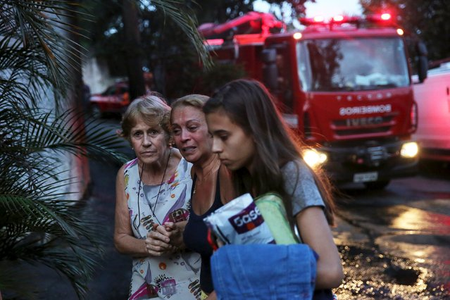 Marcia Carrara (C), 64, the owner of a house where a small airplane crashed into, cries next to a fire engine in São Paulo, Brazil, March 19, 2016. (Photo by Nacho Doce/Reuters)