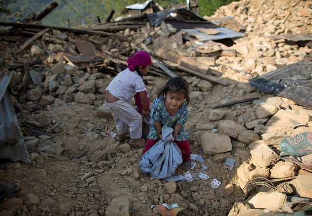Shamjana, 5, (R) and Reshmila, 8, pick up rubble as they play at the site of their collapsed house after an earthquake in a village in Sindhupalchowk, Nepal, May 2, 2015. (Photo by Danish Siddiqui/Reuters)