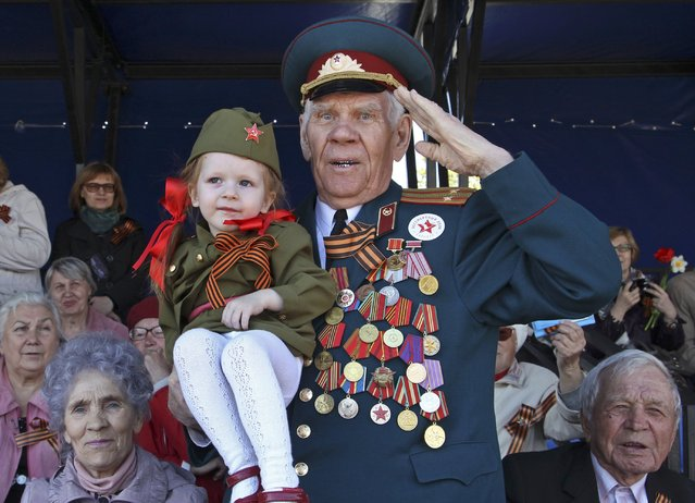 A World War Two veteran salutes as he watches the Victory Day parade in Barnaul, Russia, May 9, 2015. (Photo by Sergei Karpukhin/Reuters)