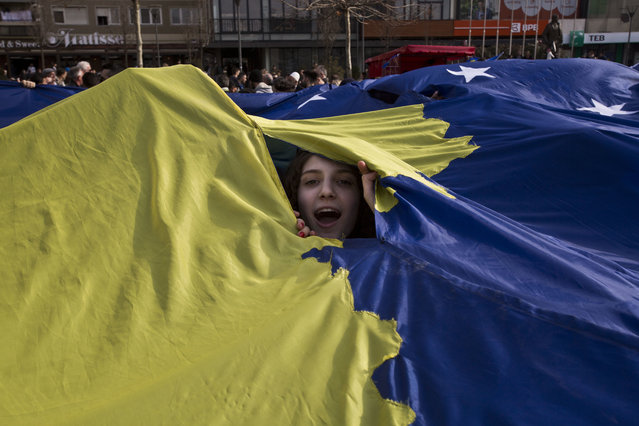 A Kosovo girl peers through a giant Kosovo flag being displayed during the celebration of the 9th anniversary of the independence in capital Pristina on Friday, February 17, 2017. Kosovo declared independence from Serbia on Feb. 17, 2008 and has so far been recognized by 113 countries, including the United States and a majority of European Union members. (Photo by Visar Kryeziu/AP Photo)