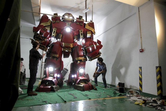 "Xing Yile (L), a 26-year-old middle school art teacher, works with his friend on their homemade replica of the ""Hulkbuster"" Iron Man armour from the movie ""Avengers: Age of Ultron"", at an underground parking lot in Zhengzhou, Henan province, China, May 12, 2015. The 3.4-metre-tall replica is made of over 100 fiber-reinforced plastic components. It took Xing and his friends two months to put them together after watching the trailer of the movie in March, local media reported. (Photo by Reuters/Stringer)"