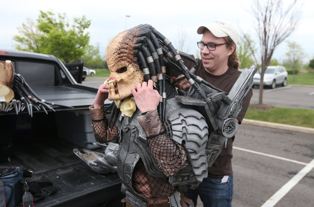 Chris Holly, right, adjusts the Predator costume of Bryan Varicalli before they attend the Motor City Comic Con at the Suburban Collection Showcase, Friday, May 15, 2015, in Novi, Mich. (Photo by Carlos Osorio/AP Photo)