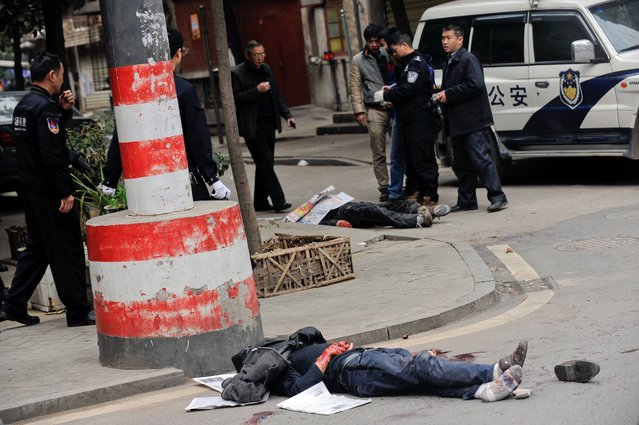 Bodies of victims lie on the ground as policemen investigate the crime scene after a knife attack in Changsha, in southern China's Hunan province, Friday, March 14, 2014. A fight between two food stall owners at a market in southern China on Friday left five people hacked to death and one person fatally shot by police, authorities said. The identity of the food stall owners was not immediately clear. (Photo by AP Photo/STR)