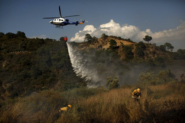 A helicopter drops water over a wildfire as firefighters work to contain it in Benahavis, southern Spain, May 19, 2015. (Photo by Jon Nazca/Reuters)