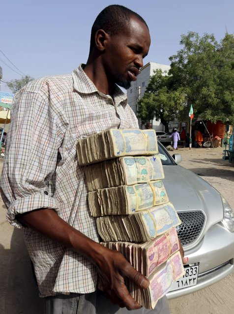 A man carries bundles of local currency near a money exchange bureau where $100 U.S. dollars change for 750,000 Somaliland shillings in Hargeysa May 19, 2015. (Photo by Feisal Omar/Reuters)