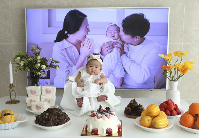 In this April 9, 2019, photo, Lee Dong Kil's daughter Lee Yoon Seol sits to celebrate her the 100th day of the birth at Lee's house in Daejeon, South Korea. Just two hours after Lee's daughter was born on New Year's Eve, the clock struck midnight, 2019 was ushered in, and the infant became 2-years-old. She wasn't alone, though it happened for her quicker than most: Every baby born in South Korea last year became 2 on Jan. 1. (Photo by Ahn Young-joon/AP Photo)