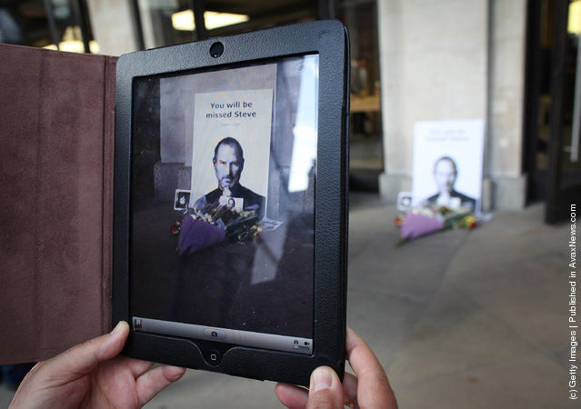 A man uses an ipad to photograph tributes to Apple Computer co-founder Steve Jobs outside The Apple Store