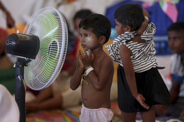 A Rohingya migrant child stands in front a fan at a temporary shelter in Kuala Langsa, Aceh province, Indonesia, Sunday, May 24, 2015. Thousands of migrants – about half of them Bangladeshi and the others minority Rohingya Muslims from Myanmar – have landed ashore in Indonesia, Malaysia and Thailand since May 10. (Photo by Tatan Syuflana/AP Photo)