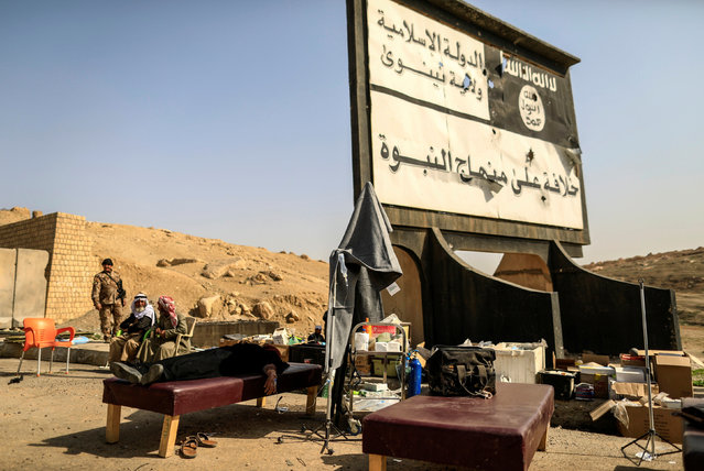 """A displaced woman lies down at a field hospital beneath a billboard erected by Islamic State's militants. The billboard reads, """"There is No God Only God. Islamic State Nineveh Governorate"""", in western Mosul, Iraq March 2, 2017. (Photo by Zohra Bensemra/Reuters)"""