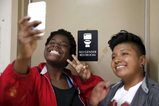 Kween Robinson, 17, (L) and Alonzo Hernandez, 16, pose for a selfie in front of the first gender-neutral restroom in the Los Angeles school district, which they helped lobby for, at Santee Education Complex high school in Los Angeles, California, U.S., April 18, 2016. (Photo by Lucy Nicholson/Reuters)