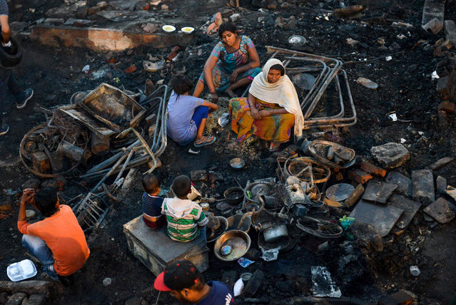 Indian slum dwellers look for their belongings after a fire broke out at their hutments in Amritsar on June 27, 2019. Hundred of hutments were burnt and no casualties reported in the incident, local reports said. (Photo by Narinder Nanu/AFP Photo)