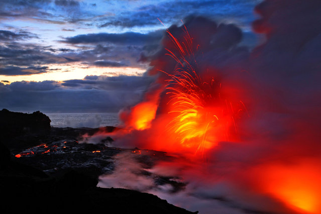 Two daredevil photographers have risked their lives to become the first people to capture the explosive moment fiery lava crashes into the sea – while in the water themselves. Fearless duo Nick Selway, 28, and pal CJ Kale, 35, brave baking hot 110F (43,3C) waters to snap the amazing images – standing just feet away from scalding heat and floating lava bombs.(Photo by Nick Selway/CJ Kale/Caters News Agency)