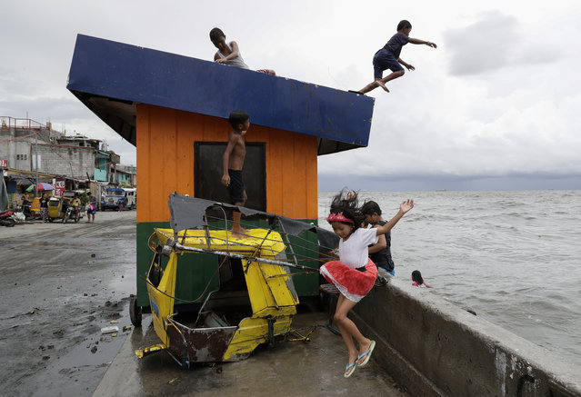 Children jump into the water despite strong waves after a strong downpour at Manila's bay, Philippines, Wednesday, July 17, 2019. Schools in metropolitan Manila have been suspended as Tropical Storm Danas, locally named Falcon, continue to enhance the southwest monsoon as it maintains its strength bringing heavy rains over parts of Luzon and Visayas according to the Philippine Atmospheric Geophysical and Astronomical Services Administration. (Photo by Aaron Favila/AP Photo)