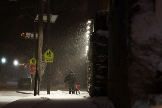 A man salts a sidewalk during a snowstorm, Tuesday, March 14, 2017, in Jersey City, N.J. (Photo by Julio Cortez/AP Photo)