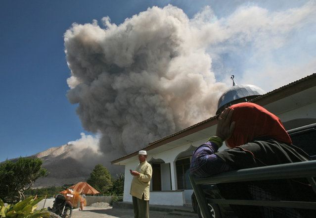 A man checks his mobile phone as Mount Sinabung spews volcanic materials in Tiga Serangkai, North Sumatra, Indonesia, Saturday, June 27, 2015. The volcano has spewed hot lava almost daily since its alert status was raised early this month to the highest level. Thousands of villagers whose homes are in the danger zone have been evacuated since then to safer areas. (Photo by Binsar Bakkara/AP Photo)