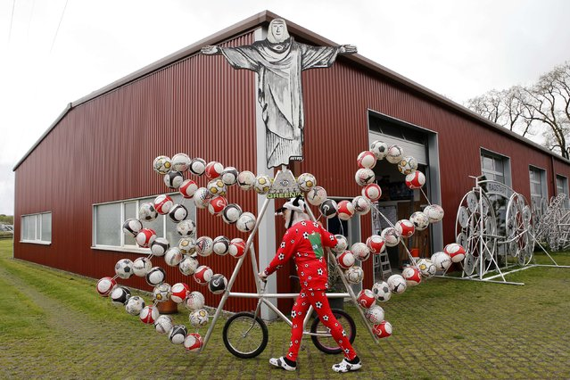 """German bicycle designer Didi Senft, also known as """"El Diablo"""", pushes out his new bicycle creation to commemorate the 2014 FIFA World Cup, in the town of Storkow, southeast of Berlin April 18, 2014. (Photo by Fabrizio Bensch/Reuters)"""