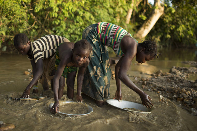 Girls pan for gold in a stream next to a local mine near the village of Game, about 230 kilometres north of the capital Bangui April 24, 2014. (Photo by Siegfried Modola/Reuters)
