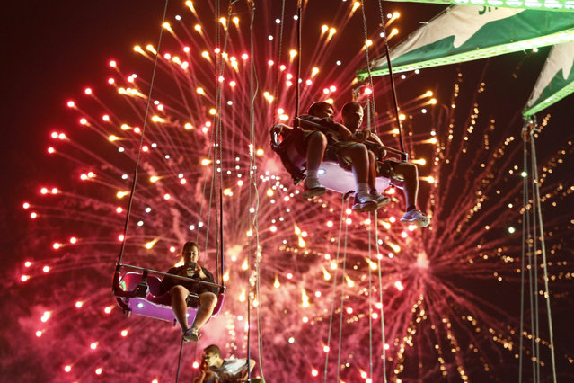 People hang from the Sky Flyer ride at the State Fair Meadowlands during a Fourth of July fireworks display, Friday, July 3, 2015, in East Rutherford, N.J. (Photo by Julio Cortez/AP Photo)