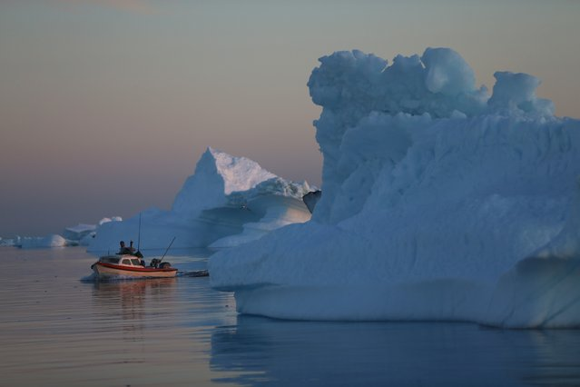 A fishing boat navigates past icebergs that broke off from the Jakobshavn Glacier on July 23, 2013 in Ilulissat, Greenland. (Photo by Joe Raedle/Getty Images)
