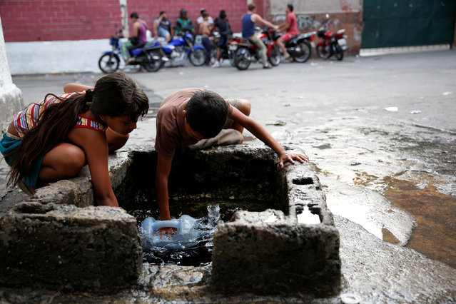 "Children fill plastic containers with water from a well on a street, close to a neighbourhood called ""The Tank"" in the slum of Petare in Caracas, Venezuela, March 17, 2016. (Photo by Carlos Garcia Rawlins/Reuters)"