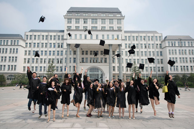 Students throw their caps in the air as friends take photos following a graduation ceremony at the private Kade College Capital Normal University on the outskirts of Beijing on June 26, 2013. Despite a boom in student numbers in recent years, many graduates from second and third-tier institutions face considerable employment uncertainty in an economy largely fuelled by a blue-collar workforce. (Photo by Ed Jones/AFP Photo)