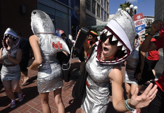 """Women promoting """"Sharknado 3"""" dance on Fifth Avenue on Preview Night at the 2015 Comic-Con International held at the San Diego Convention Center Wednesday, July 8, 2015, in San Diego. (Photo by Denis Poroy/Invision/AP Photo)"""