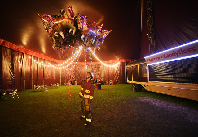 """Alexandre Lupu sells balloons at the end of the Zippos Circus show in Blackheath in London, Britain, 14 April 2017. Their latest show, """"Jigit!"""" showcases a wide range of acts from knife throwing, and swinging trapeze, to Cossack horse riders from Kahzakstan and motorcycle daredevils from Brazil. The Zippos is one of Britain's favorite family circus and has been touring the United Kingdom for more than 30 years. (Photo by Facundo Arrizabalaga/EPA)"""