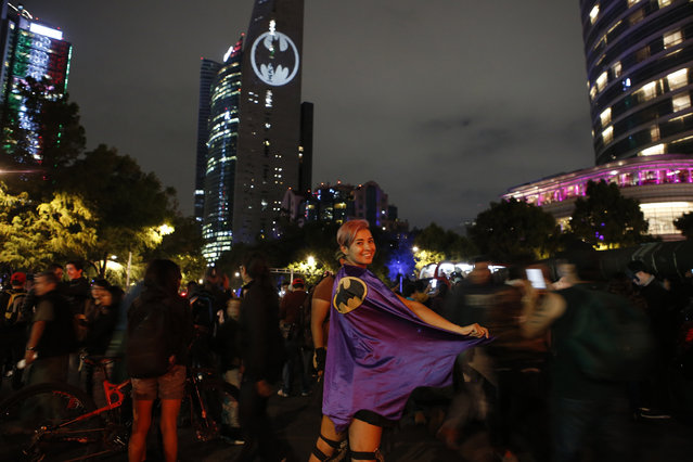 Stephanie Salgado poses with her cape during the lighting of a Bat-signal commemorating Batman's 80th anniversary in Mexico City, Saturday, September 21, 2019. (Photo by Ginnette Riquelme/AP Photo)