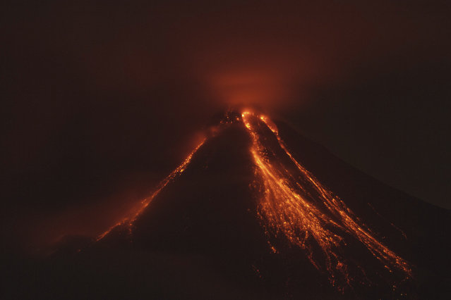 Lava flows down the banks of the Colima Volcano, also known as the Volcano of Fire, near the town of Comala, Mexico, Friday, July 10, 2015. The Colima volcano has erupted, spewing ash more than 4 miles (7 kilometers) into the air and releasing some quantity of lava. People were advised to recognize a 3-mile (5-kilometer) perimeter around the peak. (Photo by Sergio Tapiro Velasco/AP Photo)