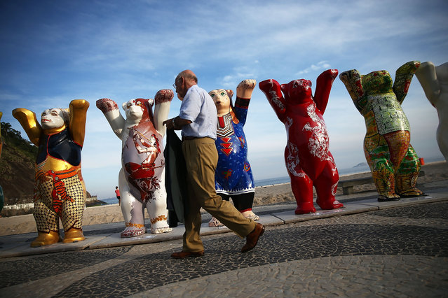 A man walks past some of the 145 bear sculptures that form the 'United Buddy Bears' exhibition along famed Copacabana beach on May 6, 2014 in Rio de Janeiro. The project promotes tolerance in the world with the two-meter tall sculptures painted by artists from United Nations member states. The show officially opened today and will run through the 2014 FIFA World Cup which begins June 12. (Photo by Mario Tama/Getty Images)