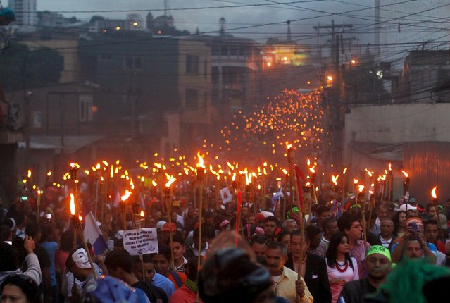 Demonstrators hold torches during a march to demand the resignation of Honduras' President Juan Hernandez in Tegucigalpa, July 10, 2015. Thousands Hondurans poured onto the streets of the capital Tegucigalpa for seventh Friday in a row to demand the resignation of President Juan Orlando Hernandez over a $200 million corruption scandal at the Honduran Institute of Social Security. (Photo by Jorge Cabrera/Reuters)