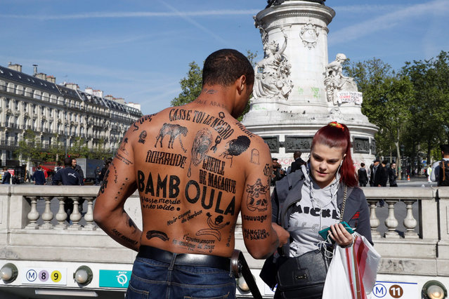 A man with his body covered with racist insults gives a flyer to a woman during an event organized by the Conseil Representatif des Associations Noires de France - CRAN (Representative Council of France' s Black Associations) to protest against racism, on the place de la Republique in Paris on April 24, 2017, one day after moderate candidate Emmanuel Macron won the first round of France' s presidential election and looked set to triumph in the run- off against far- right candidate Marine Le Pen next month. (Photo by Francois Guillot/AFP Photo)