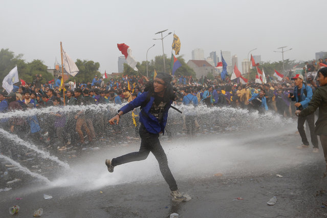 Student protesters are sprayed with a police water cannon truck during a protest outside the parliament in Jakarta, Indonesia, Tuesday, September 24, 2019. Police fired tear gas and water cannons Tuesday to disperse thousands of rock-throwing students protesting a new law that they said has crippled Indonesia's anti-corruption agency. (Photo by Tatan Syuflana/AP Photo)