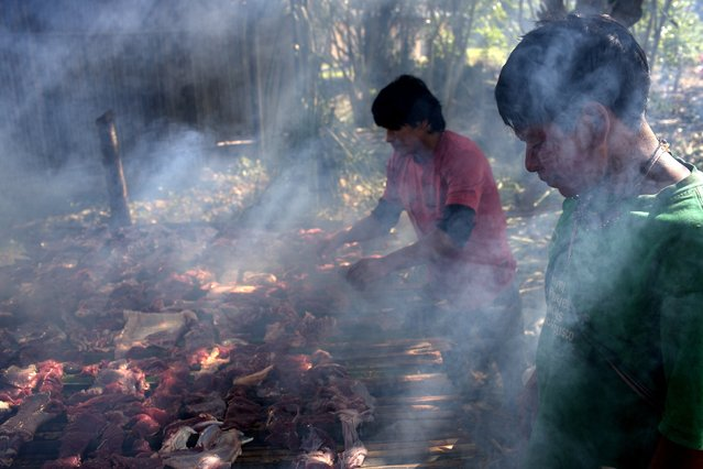 In this June 22, 2015 photo, Ashaninka Indian men smoke meat on a grill made from bamboo canes, in the Otari Nativo village, Pichari, Peru. The strips of meat come from a cow that was donated by municipal authorities to mark the 44th anniversary of their community's founding. (Photo by Rodrigo Abd/AP Photo)