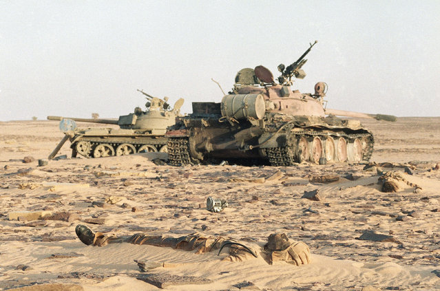 In this March 23, 1987 file photo, the body of a Libyan tank driver lies partly buried in the sands of the Sahara Desert, near Quadi-Doum, northern Chad. In the background are two Soviet-made T-55 tanks, abandoned after the forces of Chad's President Hissene Habre overran Libyan forces. (Photo by Laurent Rebours/AP Photo)