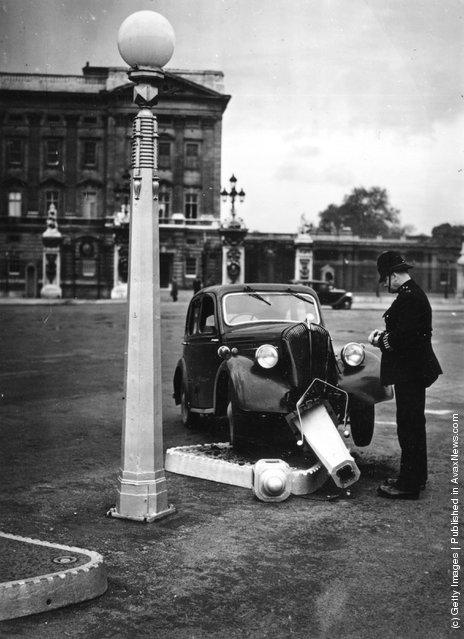 1939: A policeman views a car crashed into a traffic island outside Buckingham Palace