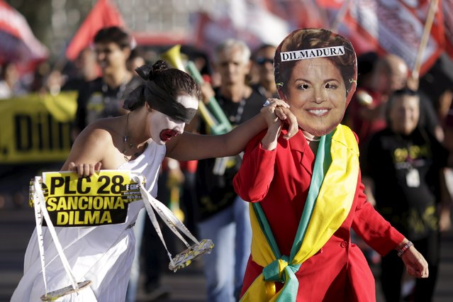 A government employee of the Judiciary, dressed as Brazil's Dilma Rousseff, holds another employee dressed as the Statue of Justice during a protest asking for a wage Increase in front of the Planalto Palace in Brasilia July 20, 2015. (Photo by Ueslei Marcelino/Reuters)