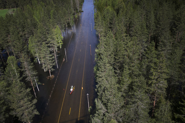 Two men paddle in a canoe on a flooded road in Trysil, Norway, on May 26, 2014. Rain and melted snow have increased the water level in the river Trysilelva. (Reuters/Heiko Junge/NTB Scanpix)