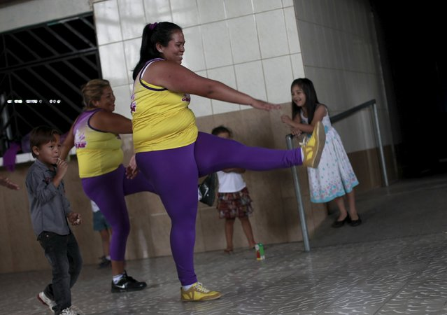 Hazel Castillo, takes part in an aerobics class next to her son Heiner Jaen, in Los Guidos de Desamparados July 23, 2015. (Photo by Juan Carlos Ulate/Reuters)