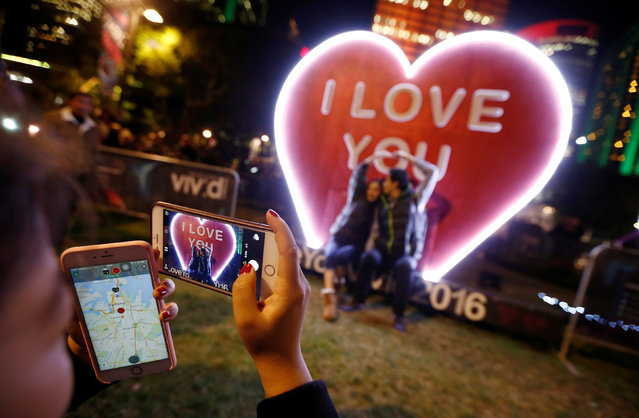 A couple have their picture taken in front of an 'I Love You' installation during the opening night of the annual Vivid Sydney light festival in Sydney, Australia May 27, 2016. (Photo by Jason Reed/Reuters)