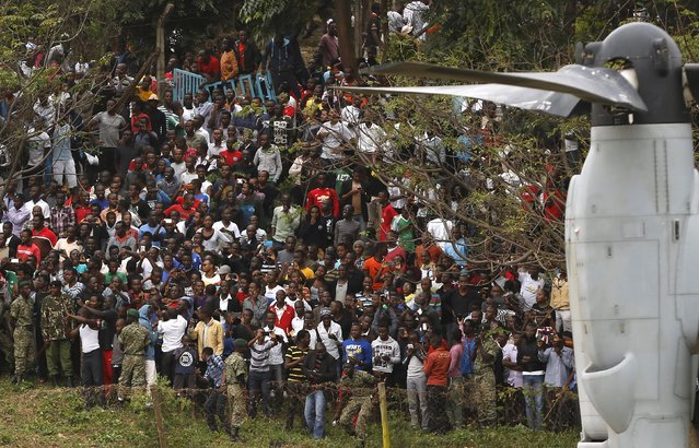 A crowd watches the compound where U.S. President Barack Obama's Marine One helicopter (not pictured) had just landed in downtown Nairobi, Kenya July 25, 2015. (Photo by Jonathan Ernst/Reuters)