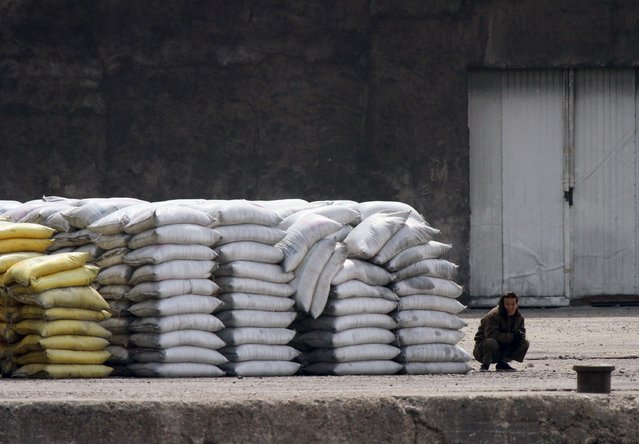 A North Korean guards goods from China on the banks of the Yalu River, near the North Korean town of Sinuiju, opposite the Chinese border city of Dandong, April 6, 2015. (Photo by Jacky Chen/Reuters)