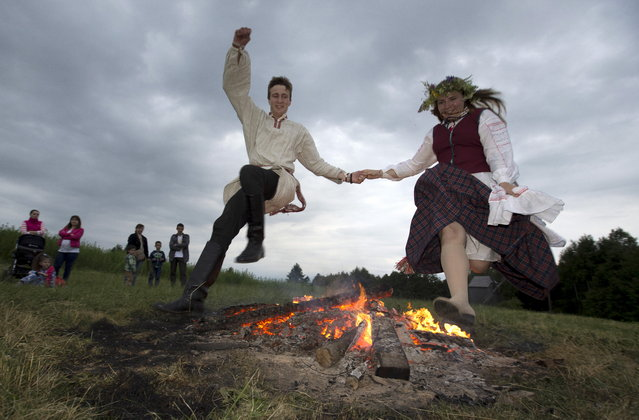 People jump over the campfire as they take part in the Ivan Kupala festival near the village of Ozertso, on the outskirts of Minsk, Belarus, June 20, 2015. The traditional festival celebrates the summer solstice with overnight festivities such as singing and dancing before jumping over campfires, which people believe will purge them of their sins and make them healthier. (Photo by Vasily Fedosenko/Reuters)