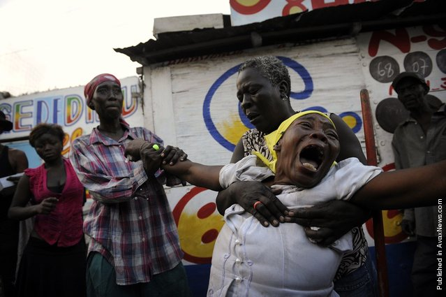 Armante Cherisma cries in front of the body of her daughter, Fabienne, 15 years old, killed by a policeman during lootings in the Marthely Seiee street January 19, 2010 in Port-au-Prince