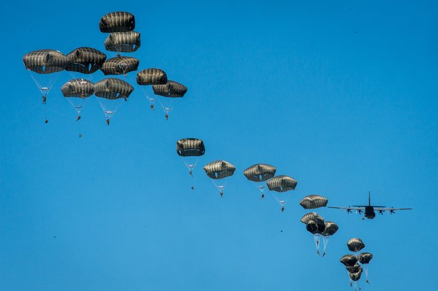 US paratroopers from the 82 Airborne Division and Lockheed C-130 Hercules aircraft are seen in the air during the Swift Response-16 part of the NATO Anaconda-16 exercise at the military area near Torun, Poland, 07 June 2016. About 2 thousand paratroopers from Poland, USA and Great Britain took part in a landing exercise as part of the The Polish-led multinational exercise Anaconda-16, conducted with allies and partners from 24 countries between 07 and 17 June 2016, which is to test and enhance the capabilities of NATO countries to quickly respond to threats regardless of distance and origin. (Photo by Tytus Zmijewski/EPA)