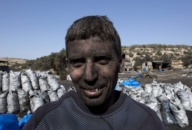In this photo taken Monday, November 21, 2016, Palestinian laborer Sami Abu Baker, 35, who has a fifteen years service in the charcoal factories, poses for a picture during a day work, in the West Bank town of Yabad, near Jenin. For years, residents of central Israel have been complaining about the air pollution emanating from nearby Palestinian factories in the West Bank and the potential health hazards they pose. But now that authorities have finally cracked down, shutting the worst offending charcoal plants, Palestinians say hundreds have been put out of work in a swift stamp of the military occupation. (Photo by Nasser Nasser/AP Photo)