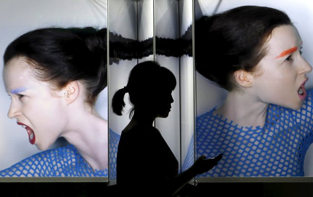 A woman holding her mobile phone walks past a display window outside a cosmetic company at Tokyo's Ginza shopping district in Japan, July 20, 2015. (Photo by Yuya Shino/Reuters)